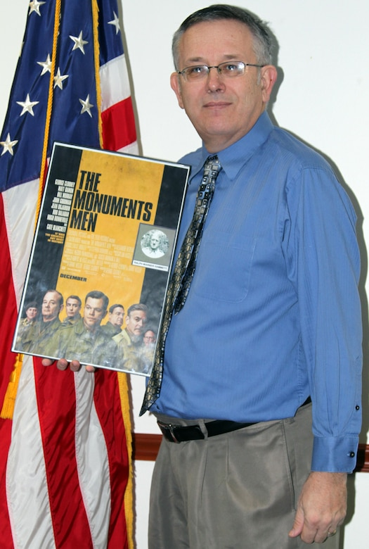 "Little Rock District Deputy District Counsel Ralph Allen stands with a movie poster for ""The Monuments Men,"" a current film about the dangerous job his grandfather, Ralph W. Hammett, held during World War II."