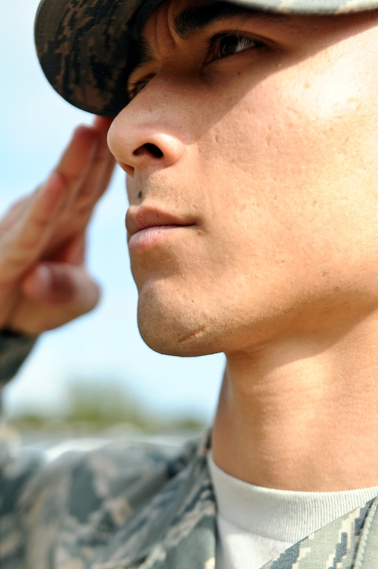 Senior Airman Shokhrukh Dadajanov, Hurlburt Field honor guardsman, renders a salute during a retreat ceremony on Hurlburt Field, Fla., Feb. 10, 2014. Military members in uniform should assume the position of attention and salute when the national anthem plays. (U.S. Air Force photo/Senior Airman Michelle Vickers)