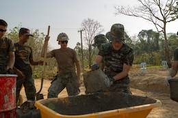 Republic of Korea Cpl. Kim Seungju dumps wall plaster into a wheel barrow as U.S. Navy Petty Officer 3rd Class Shianne M. Chlupacek observes Feb. 10 at Wut Khun Song school near Ban Chan Krem, Kingdom of Thailand. U.S. service members joined forces with Royal Thai Marines and Republic of Korea Marines for a community relations project which started Jan. 25 and is expected to be completed Feb. 20. The program is part of Exercise Cobra Gold 2014, a multinational and multiservice exercise that takes place annually in the Kingdom of Thailand and was developed by the Thai and U.S. militaries. Seungju is a combat engineer with 1st Engineer Battalion, ROK Marine Division. Chlupacek is a steelworker with Seabees' Naval Mobile Construction Battalion 3, 1st Naval Construction Group.
