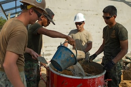 A U.S. sailor, airman and Royal Thai Marines mix wall plaster Feb. 10 at Wut Khun Song school near Ban Chan Krem, Kingdom of Thailand. The service members joined forces for a community relations project in which three new classrooms were built. The community relations project started Jan. 25 and is expected to be completed Feb. 20. The program is part of Exercise Cobra Gold 2014, a multinational and multiservice exercise that takes place annually in the Kingdom of Thailand and was developed by the Thai and U.S. militaries. The Royal Thai Marines are combat engineers with Combat Engineer Battalion, 3rd Royal Thai Marine Division. The U.S. sailors are with the Seabees' Naval Mobile Construction Battalion 3, 1st Naval Construction Group.