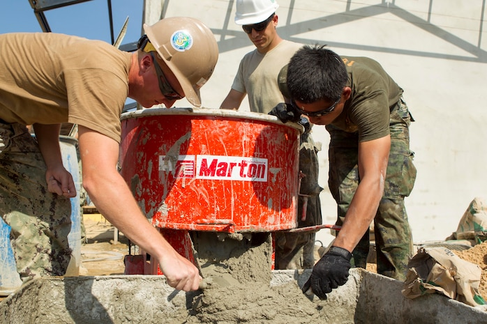 U.S. Navy Petty Officer 3rd Class Ethan P. Kerber, left, U.S. Air Force Senior Airman Carlos E. Flores, center, and Royal Thai Petty Officer 2nd Class Tam Wanchai prepare wall plaster Feb. 10 at a Wut Khun Song school near Ban Chan Krem, Kingdom of Thailand. The service members joined forces for a community relations project in which three new classrooms were built. The community relations project started Jan. 25 and is expected to be completed Feb. 20. The program is part of Exercise Cobra Gold 2014, which is a multinational and multiservice exercise that takes place annually in the Kingdom of Thailand and was developed by the Thai and U.S. militaries. Wanchai is a combat engineers with Combat Engineer Battalion, 3rd Royal Thai Marine Division the Kerber is a steelworker with the Seabees' Naval Mobile Construction Battalion 3, 1st Naval Construction Group and Flores is an electrical power production journeyman with 35th Civil Engineer Squadron, 35th Fighter Wing.