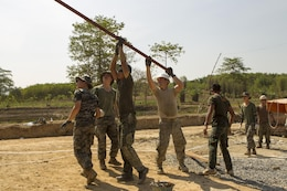 U.S. service members, Royal Thai Marines and Republic of Korea Marines work together to lift a piece of roofing material Feb. 10 Wut Khun Song school near Ban Chan Krem, Kingdom of Thailand. The material will serve as the base to the rest of the roof when the school is completed. The community relations project started Jan. 25 and is expected to be completed Feb. 20. The program is part of Exercise Cobra Gold 2014, which is a multinational and multiservice exercise that takes place annually in the Kingdom of Thailand and was developed by the Thai and U.S. militaries. The Royal Thai Marines are combat engineers with Combat Engineer Battalion, 3rd Royal Thai Marine Division the U.S. service members are with the Seabees' Naval Mobile Construction Battalion 3, 1st Naval Construction Group.