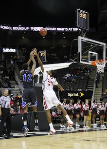 Elijah Childs, 24, a Raytown South High School Cardinal forward, attempts to block a shot by Jailen Gill, 12, a Raytown High School Bluejay center and forward, during the Time Warner Sports Channel Showcase at the Sprint Center here Jan. 20, 2014. Fourteen schools participated in the showcase. Marine recruiters from Recruiting Sub-Stations Overland Park, Independence, Gladstone and Topeka were on hand with a setup display table and pull-up bar.