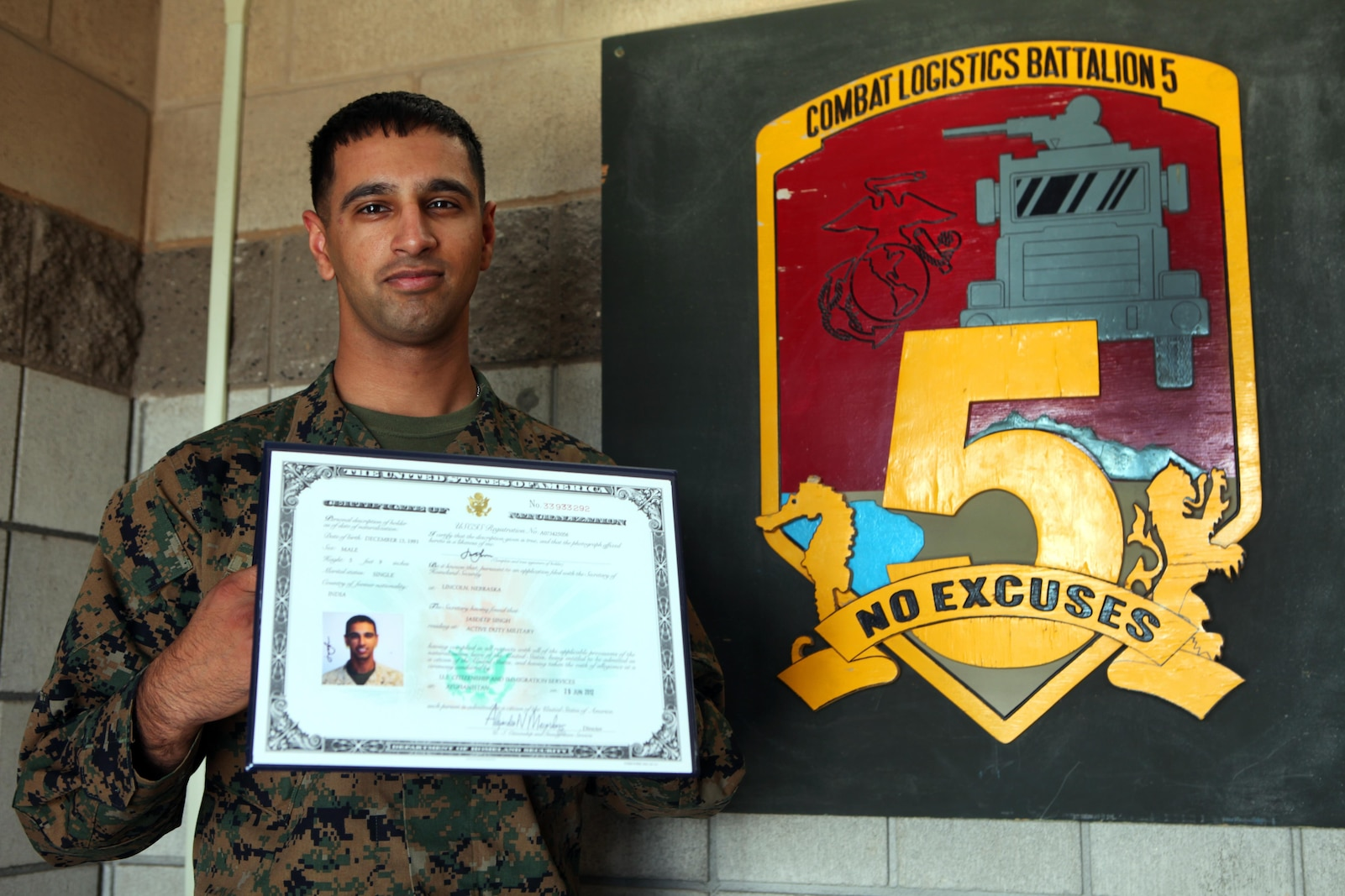 Corporal Jasdeep Singh, supply administrative chief, Combat Logistics Regiment 5, 1st Marine Logistics Group, displays his certificate of naturalization in front of the CLB-5 logo aboard Camp Pendleton, Calif., Feb. 4, 2014. Singh became a US citizen while serving in Afghanistan in 2012.