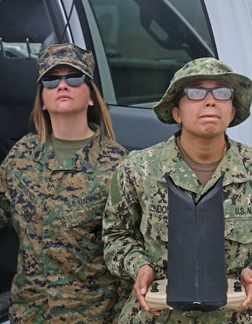Sergeant Cynthia Zermeno, (left) a training noncommissioned officer with 1st Medical Battalion, Combat Logistics Regiment 15,1st Marine Logistics Group, and Navy Petty Officer 3rd Class Nathalia Londono, (right) a master at arms with Marine Corps Security Forces Battalion, land an unmanned aerial vehicle during a UAV course aboard Camp Pendleton, Calif., Jan. 30, 2014. The UAV course is two weeks long and focuses on familiarizing Marines and sailors with the equipment needed to control a UAV primarily through practical application.