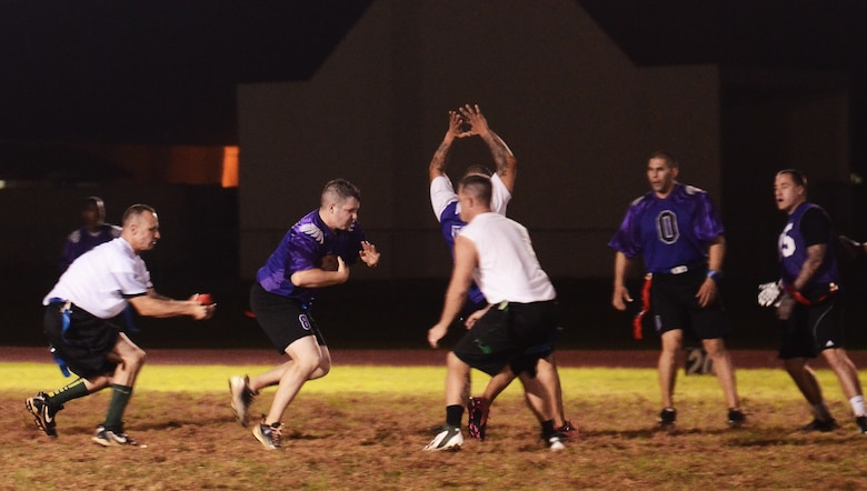Ernest Clemons, 36th Security Forces Squadron, attempts to evade his opponents during an intramural flag football playoff game between 36th SFS and 736th Security Forces Squadron on Andersen Air Force Base, Guam, Jan. 14, 2014. The championship game is scheduled for Jan. 17 at 6 p.m. (U.S. Air Force photo by Airman 1st Class Mariah Haddenham/Released)