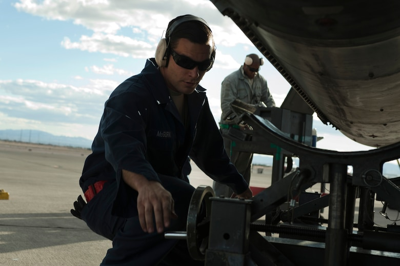 U.S. Air Force Tech Sgt. Donnie McGuark, 57th Aircraft Maintenance Squadron Viper Aircraft Maintenance Unit crew chief, lowers a lift used to install a new F-16 Fighting Falcon fuel tank on the flightline Feb. 10, 2014, at Nellis Air Force Base, Nev. The lift has a front and back crank in order to provide an easier installation of fuel tanks. (U.S. Air Force photo by Airman 1st Class Timothy Young)