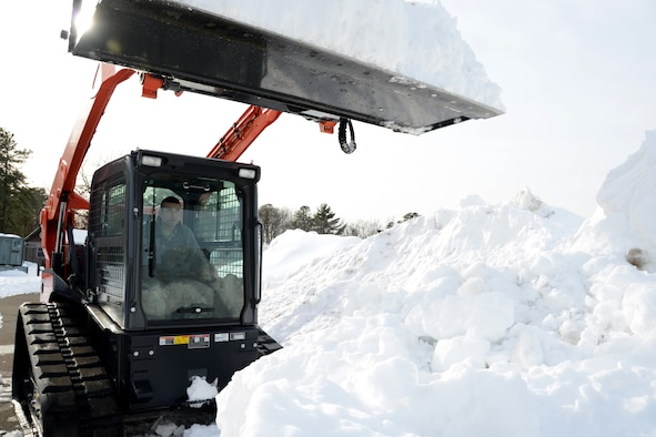 Senior Airman Christopher Cangemi, 103rd Civil Engineer Squadron, uses a new Kabota skid steer machine to clear snow from an accumulation point that could soon host additional snow expected to fall overnight on Feb. 12, 2014.  Despite their current high state of readiness and their proven track record of storm recovery service to the state and community, the unit will soon conduct a three-day course to train additional volunteers from other units of the Connecticut Air National Guard to increase the available pool of skilled team members for recovery operations in the event of a natural disaster, on or off base.  (U.S. Air National Guard photo by Master Sgt. Erin McNamara)