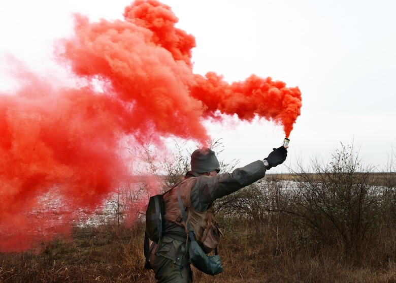Lt. Col. Christopher Austin, 510th Fighter Squadron commander, utilizes red distress smoke to signal his location to a U.S. Army 12th Combat Aviation Brigade UH-60 Black Hawk helicopter during a simulated combat search and rescue, Jan. 28, 2014, at Cellina Meduna training grounds near Maniago, Italy.  (U.S. Air Force/Airman 1st Ryan Conroy)