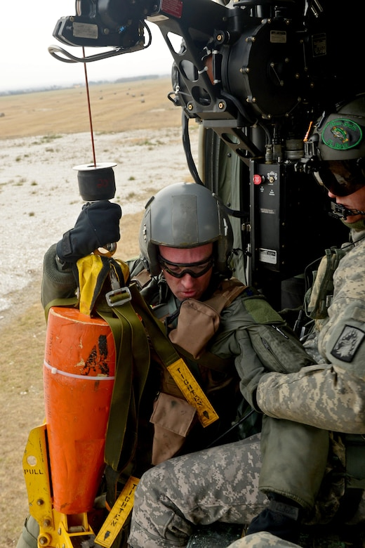 "Lt. Col. Christopher Austin, (from left) is pulled onto a UH-60 Black Hawk helicopter by U.S. Army Sgt. Keith Dishman, 12th Combat Aviation Brigade crew chief during a joint-service combat search and rescue training mission, Jan. 28, 2014 at Cellina Meduna, Italy. After successfully evading opposing forces and communicating with assets in the air, isolated Airmen were extracted from ""hostile"" areas by the 12th CAB. (U.S. Air Force photo/Senior Airman Briana Jones)"