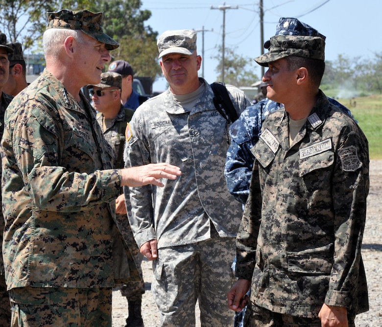 U.S. Marine Corps Gen. John F. Kelly, Commander, U.S. Southern Command, visits with a member of the Honduran navy while touring a Honduran naval base at Puerto Castilla, Honduras, Feb. 12, 2014.  Kelly and a delegation of U.S. Department of State and U.S. and Honduran military leaders, including U.S. Ambassador to Honduras Lisa Kubiske, Honduran Maj. Gen. Fredy Diaz, Joint Chief of the Honduran Military, and Honduran Rear Admiral Hector Caballero, Honduran Navy Commander, spent the day visiting several Honduran military facilities. Throughout the day, the delegation received briefings and had the opportunity to discuss issues with Honduran military leadership. Transportation for the day was provided by UH-60 Blackhawk helicopters from Joint Task Force-Bravo's 1-228th Aviation Regiment. (U.S. Air Force photos by Capt. Zach Anderson)