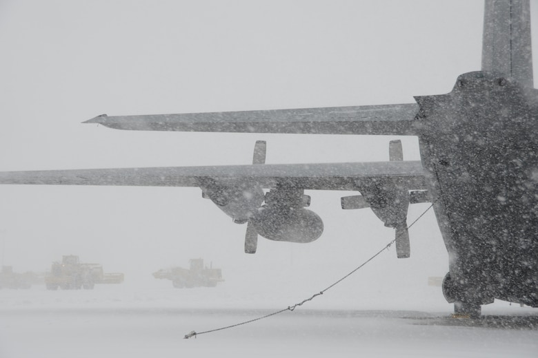 A C-130H aircraft assigned to the 103rd Airlift Wing weathers the storm during near whiteout conditions at Bradley Air National Guard Base, East Granby, Conn., as plows work to clear the flightline of the rapidly accumulating snow from a nor'easter Feb. 13, 2014. More than 200 Airmen reported to work here and at the Orange Air National Guard Station, ready to answer the call in the event the state required assistance during the height of the storm. (U.S. Air National Guard photo by Maj. Bryon M. Turner)