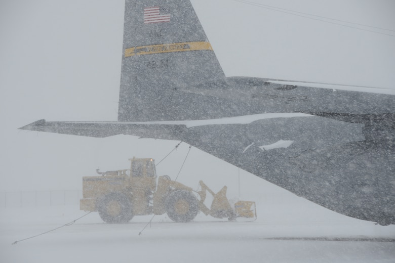 A C-130H aircraft assigned to the 103rd Airlift Wing parked at Bradley Air National Guard Base, East Granby, Conn., as a plow works to clear the flightline of the rapidly accumulating snow from a nor'easter Feb. 13, 2014. More than 200 Airmen reported to work here and at the Orange Air National Guard Station, ready to answer the call in the event the state required assistance during the height of the storm.  (U.S. Air National Guard photo by Maj. Bryon M. Turner)