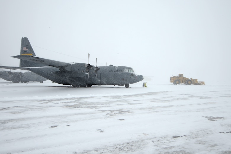 A C-130H assigned to the 103rd Airlift Wing in East Granby, Conn. weathers the storm Feb. 13, 2014, as more than a half dozen machines from the adjacent Bradley International Airport work to clear the rapdily accumulating snow from the aircraft ramp at Bradley Air National Guard Base, East Granby, Conn.  (U.S. Air National Guard photo by Master Sgt. Erin McNamara)