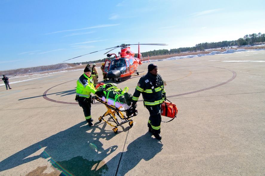 Emergency medical technicians from Atlantic City International Airport transport U.S. Air Force Maj. Jared Mandella on a stretcher during an air mishap exercise at Coast Guard Air Station Atlantic City, N.J., on Feb. 11, 2014. The exercise, which is an annual requirement for Air Station Atlantic City, involved the Coast Guard, Federal Aviation Administration, South Jersey Transportation Authority Fire Department, and the 177th Fighter Wing Fire Department. Mandella is an F-16 pilot from from the New Jersey Air National Guard's 177th Fighter Wing. (U.S. Air National Guard photo by Tech. Sgt. Matt Hecht/Released)