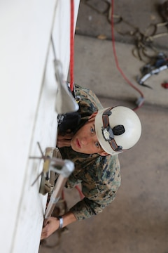 Cpl. Sean O'Toole, a tow gunner with the 11th Marine Expeditionary Unit's ground combat element, 2nd Battalion, 1st Marines, and a Mesa, Ariz. native, practices climbing a building using a hook and pole with a soft ladder and ice axe during the Assault Climber Course here Feb.12. A team of instructors trained Marines to become qualified assault climbers. Their new skillset is an asset gained for the 11th MEU's ensuing deployment later this summer.
