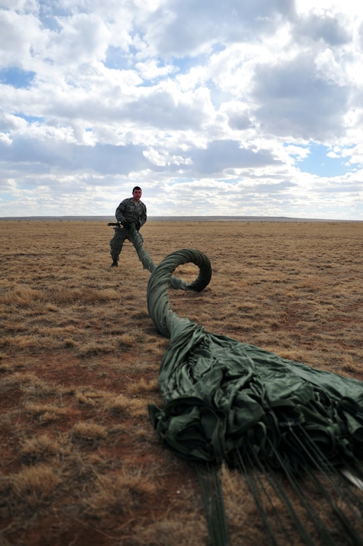 """Airman 1st Class Bradley Gann rolls a deflated parachute Feb. 4, 2014, at Melrose Air Force Range, N.M. After rolling the canopy, aerial porters """"daisy-chain"""" the lines at the end of the parachute to prevent tangling. Gann is an aerial porter with the 27th Special Operations Logistics Readiness Squadron. (U.S. Air Force photo/Airman 1st Class Shelby Kay-Fantozzi)"""