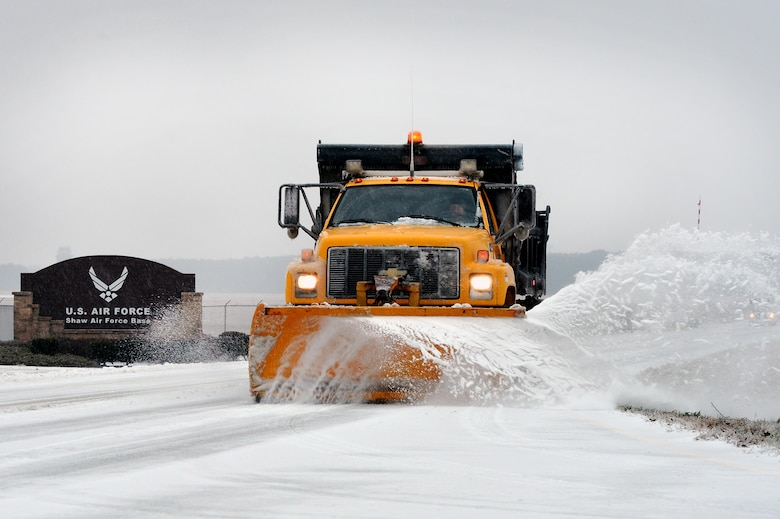 A snow plow removes snow and ice outside the base main gate Feb. 12, 2014, at Shaw Air Force Base, S.C. Though severe winter weather is rare at Shaw AFB, this winter season has presented a fair amount of snow, sleet and ice. More than once this season, base officials had to reduce manning to mission essential personnel due to inclement weather. (U.S. Air Force photo/Staff Sgt. Kenny Holston)