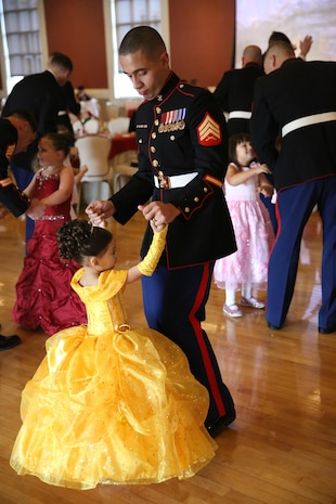 A Marine and his daughter enjoy dancing and festivities at the Tiny Miss Daddy-Daughter Dance held Feb. 8, 2014 at the Marston Pavilion aboard Marine Corps Base Camp Lejeune.