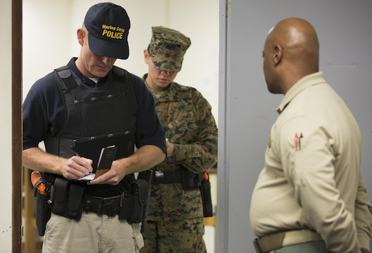 A civilian student and Marine work together in an evidence-gathering exercise with Robby D. Mask (right), an instructor at the Marine Corps Police Academy West, aboard Marine Corps Air Station Miramar, Calif., Feb. 11. Marine and civilian students work together at the academy during a 12-week course.
