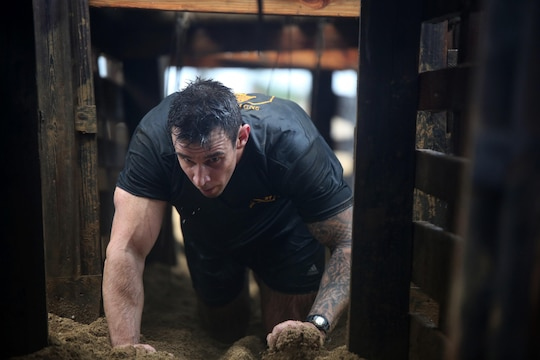 A runner in the Swamp Romp crawls through an obstacle at Fort Hase Beach aboard Marine Corps Base Hawaii Feb. 8, 2014. The event was 3.5 miles long with various obstacles along the way. (U.S. Marine Corps photo by Cpl. Sarah Dietz)