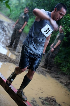 A runner crosses a balance beam over a 3-foot deep puddle of mud during the Swamp Romp Feb. 8, 2014 aboard Marine Corps Base Hawaii. (U.S. Marine Corps photo by Cpl. Sarah Dietz)