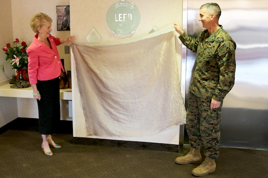 Bonnie Amos, First Lady of the Marine Corps, and Col. John Farnam, commanding officer of Marine Corps Air Station Miramar, unveil the Leadership in Energy and Environmental Design Gold plaque at the Miramar Inn aboard Marine Corps Air Station Miramar, Calif., Feb. 13. Amos toured the inn and learned about the environmentally friendly changes the facility made.