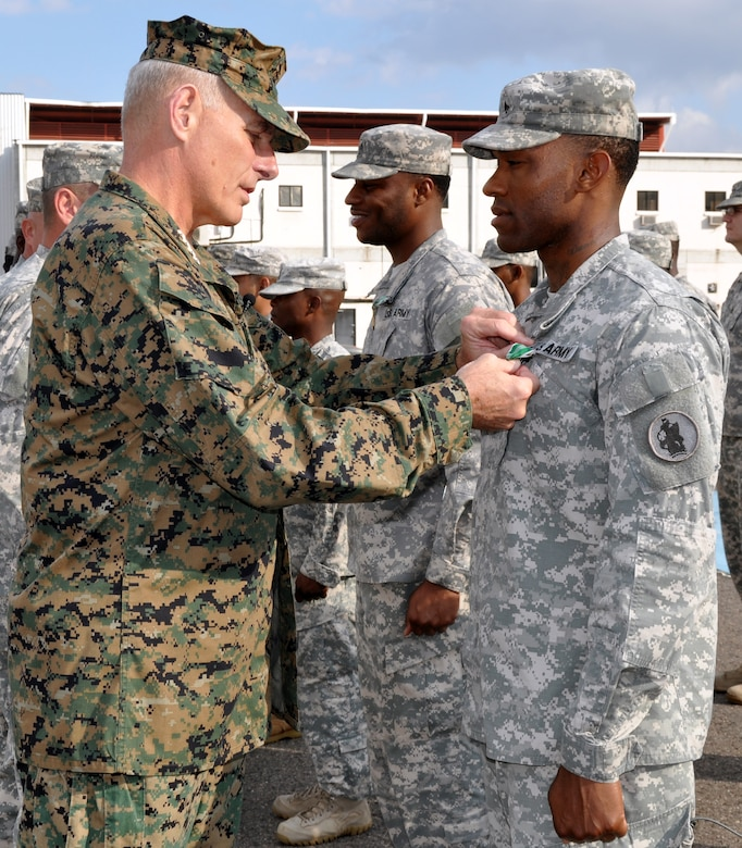 U.S. Marine Corps Gen. John F. Kelly, commander, U.S. Southern Command, presents the Army Commendation Medal to U.S. Army Sgt. Randy McKire during a Joint Task Force-Bravo promotion and awards ceremony conducted on the flightline at Soto Cano Air Base, Honduras, Feb. 13, 2014. Kelly pinned new rank on six Task Force members who were promoted during the ceremony and presented medals, including the Army Commendation Medal, the Air Force Commendation Medal, and the Army Achievement Medal, to 18 members. Following the ceremony, Kelly addressed the members of the Task Force and thanked them for their work and dedication to duty. (U.S. Air Force photo by Capt. Zach Anderson)