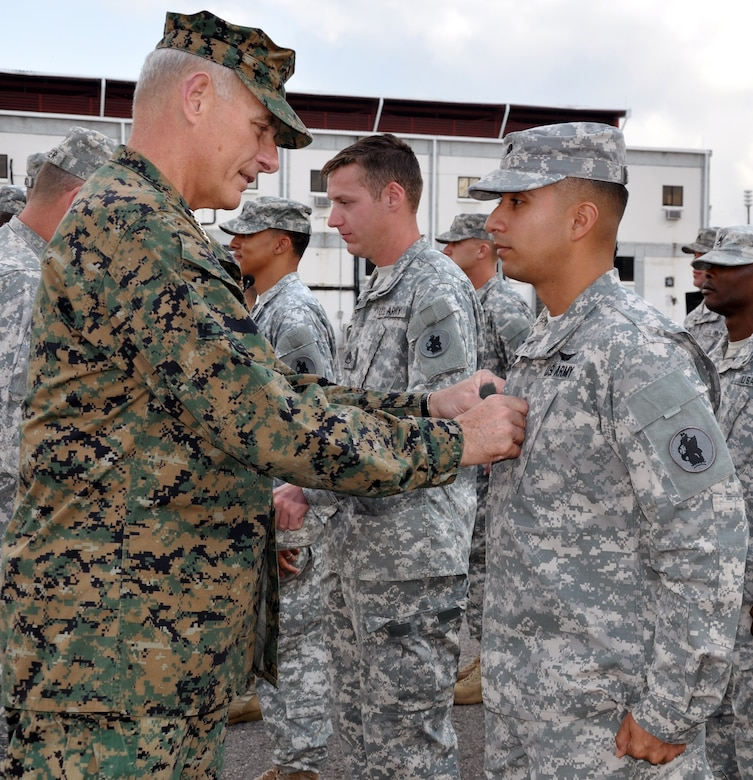 U.S. Marine Corps Gen. John F. Kelly, commander, U.S. Southern Command, pins rank on newly promoted U.S. Army Sgt. Alejandro Arellano during a promotion and awards ceremony conducted on the flightline at Soto Cano Air Base, Honduras, Feb. 13, 2014. Kelly pinned new rank on six Task Force members who were promoted during the ceremony and presented medals, including the Army Commendation Medal, the Air Force Commendation Medal, and the Army Achievement Medal, to 18 members. Following the ceremony, Kelly addressed the members of the Task Force and thanked them for their work and dedication to duty. (U.S. Air Force photo by Capt. Zach Anderson)
