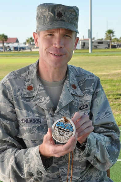 Maj. Joel Fenlason, 45th Space Wing deputy director of staff, holds up a medal he earned for running the Big Sur International Marathon in Calif. He started running marathons in 2005 when he was 31 years old. His goal was to complete 50 marathons by his 40th birthday. Now 40, he is preparing to run his 75th marathon Feb. 16. (U.S. Air Force Photo/Tech. Sgt. Erin Smith)