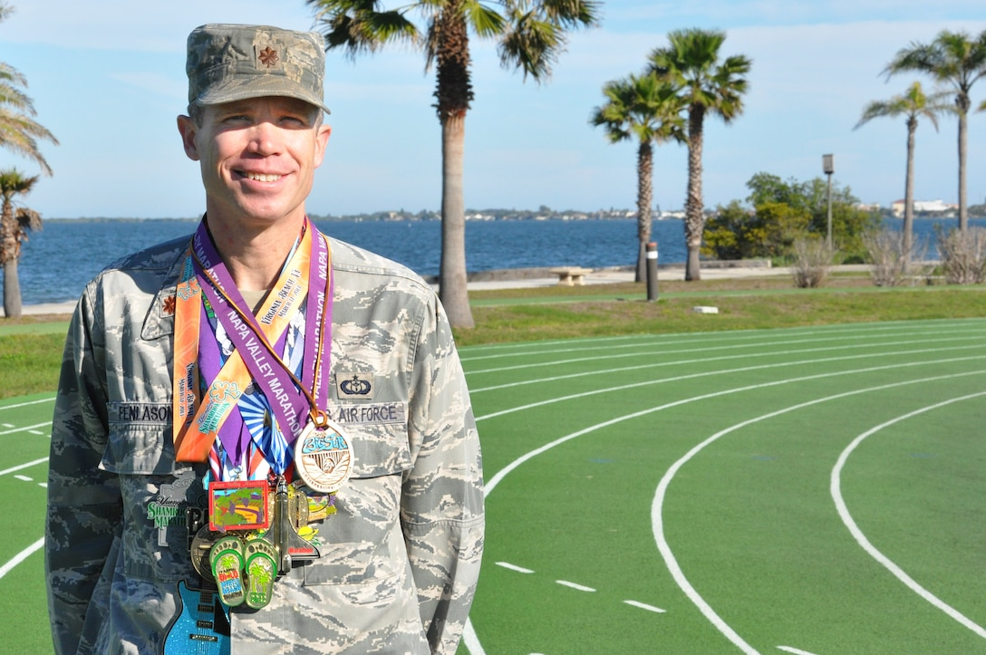 Maj. Joel Fenlason, 45th Space Wing deputy director of staff, displays some of the medals he has earned for running marathons over the past 9 years. He started running marathons in 2005 when he was 31 years old. His goal was to complete 50 marathons by his 40th birthday. Now 40, he is preparing to run his 75th marathon Feb. 16. (U.S. Air Force Photo/Tech. Sgt. Erin Smith)