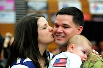U.S. Army. 1st Lt. Grant Karr, 1-135th Attack Reconnaissance Battalion, receives a kiss from his wife, Emily, as he holds his six-month old son following the unit's welcome-home ceremony at the University of Central Missouri in Warrensburg, Mo., Feb. 9, 2014. Karr deployed to Afghanistan with more than 300 other soldiers in aid of Operation Enduring Freedom. (U.S. Air Force photo by Staff Sgt. Nick Wilson/Released)