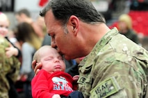 U.S. Army Sgt. 1st Class Ed Borgstadt, 1-135th Attack Reconnaissance Battalion operations NCO in charge, kisses his three-week-old grandson for the first time following the unit's welcome-home ceremony at the University of Central Missouri 