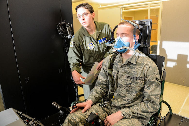 Capt. Julianne Gillespie, 62nd Airlift Wing aerospace and operational physiologist, checks the breathing of Airman 1st Class Erich Held, 62nd Medical Squadron optometry technician, doubling as a pilot using the Reduced Oxygen Breathing Device at the McChord Field clinic, Feb. 5, 2014 at Joint Base Lewis-McChord, Wash. The ROBD will ultimately replace the more expensive altitude chamber for the required re-fresher training aircrew needs every five years. (U.S. Air Force photo/Tech. Sgt. Sean Tobin)