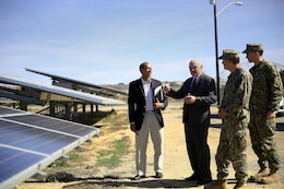 """From left, Charles Howell, Dennis McGinn, Navy Capt. Charles R. Reuning and Lt. Cmdr Ben Wainwright talk about the Phase I and Phase II photovoltaic array (solar panels) at Box Canyon, near Wire Mountain housing.   Assistant Secretary of the Navy-Energy, Installations and Environment, Dennis McGinn, visited Camp Pendleton to view the energy projects on base and to speak about energy goals for the future. """"If nothing else, I want to leave you with an appreciation for how absolutely essential and inexplicably tied our mission readiness is to the kinds of energy we have and how we use it,"""" said McGinn.    Howell is the resource efficiency manager for the base energy office.  Reuning is a facilities officer with Camp Pendleton. Wainwright is the Assistant Secretary of the Navy's aide."""