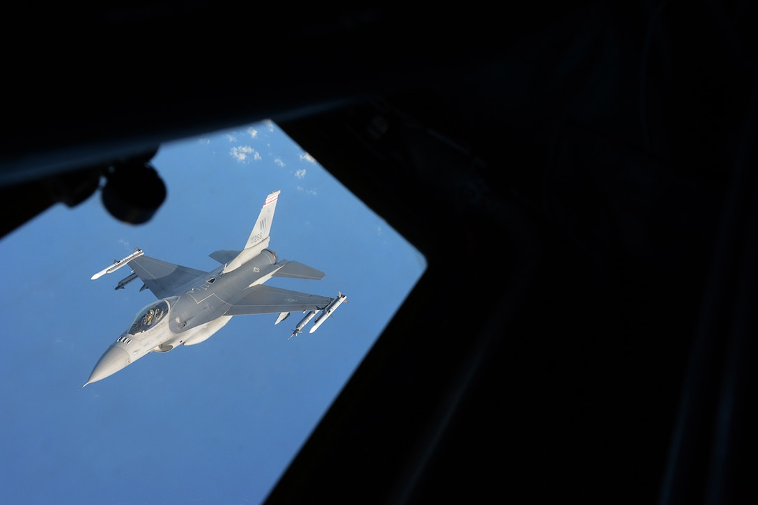An Air National Guard F-16 Fighting Falcon assigned to the 115th Fighter Wing flies past the left boom operator's window of a KC-135 Stratotanker after refueling during a training exercise near Key West, Fla., Feb. 5, 2014. The 115th FW came to Key West in February to reduce the likelihood of flight cancelations due to weather. The deployment that lasted almost two weeks allowed the pilots to test their expertise against dissimilar aircraft. (Air National Guard photo by Senior Airman Andrea F. Liechti)