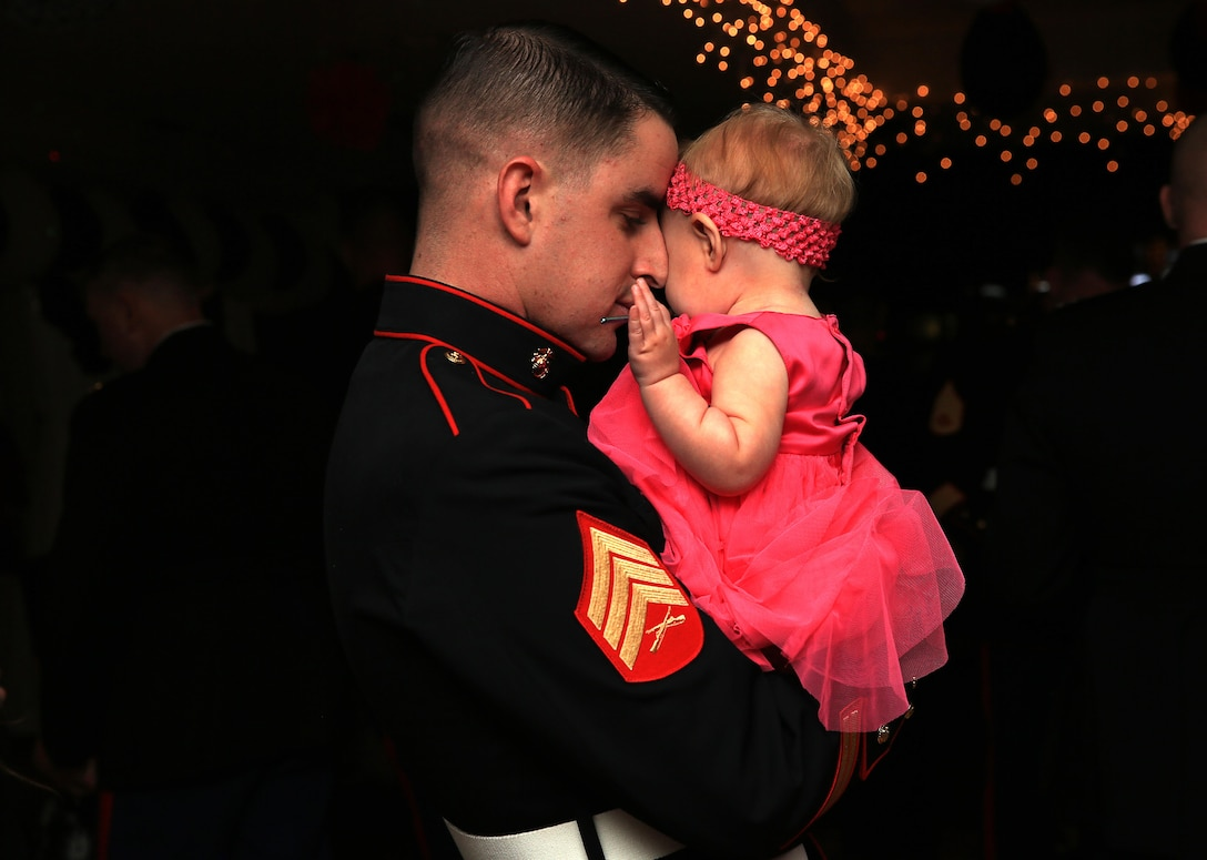 """Sgt. Juan Ramos, heavy equipment mechanic, 3rd Combat Engineer Battalion, shares an embrace with his daughter, Zuly Ramos, 8 months old, during a slow song at the """"Princess of the Castle"""" event Feb. 7, 2014, hosted at the Officers' Club. This event is the first of its kind for 3rd Combat Engineer Battalion."""