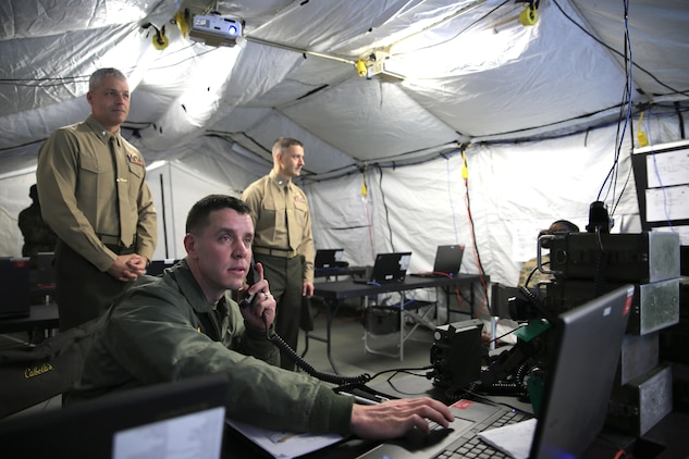 Major O.J. Weiss (lower left), the operations officer for Marine Aircraft Group 31, demonstrates the effectiveness of the communication system at a remote site to Lt. Col. Nicholas Neimer (left), commanding officer of MAG-31 Headquarters squadron, and Lt. Col. Joseph Reedy (right), the executive officer of MAG-31 Headquarters Squadron, during MAG-31's Command Post Exercise (CPX) aboard Marine Corps Air Station Beaufort, Feb. 7. The exercise was executed concurrent with Marine Division Tactics Course in order to test the capabilities of the group to conduct aviation operations from expeditionary sites and exercise tactical command and control. The ability to operate expeditiously promotes MAG-31's ability to act as the Aviation Command Element (ACE) of a Marine Air-Ground Task Force.