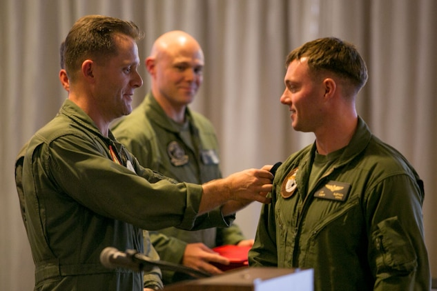 Col. William R. Lieblein, The Marine Aircraft Group 31 commanding officer, places a Marine Avation Weapons and Tactics Squadron One patch on the shoulder of a graduate of the Marine Division Tactics Course during a graduation ceremony at the Marine Corps Air Station Beaufort Officer's Club Feb. 7.