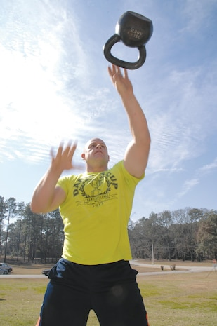 Staff Sgt. Charles Trimble works on his single arm alternating kettle bell swings during Marine Corps Systems Command's strength and endurance circuit training here, Feb. 7.