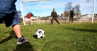 """Marines with Combat Logistics Regiment 1, 1st Marine Logistics Group, play goalie during a morning workout at Jefferson Elementary School, Feb. 13, 2014. Marines with CLR-1 and 1st Medical Battalion, volunteered their time to support more than 500 students in their new fitness program known as """"Motion."""" During their visit Marines led various events, such as push-ups, squats, soccer and basketball."""