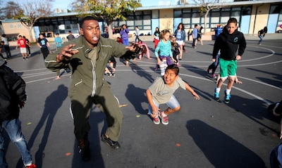 """Corporal Elijah Williams, a motor transportation mechanic with 1st Medical Battalion, 1st Marine Logistics Group, shows a student how to properly do a squat during a morning workout at Jefferson Elementary School, Feb. 13, 2014. Marines with Combat Logistics Regiment 1 and 1st Medical Bn., volunteered their time to support more than 500 students in their new fitness program known as """"Motion."""" During their stay Marines led various events, such as push-ups, squats, soccer and basketball."""