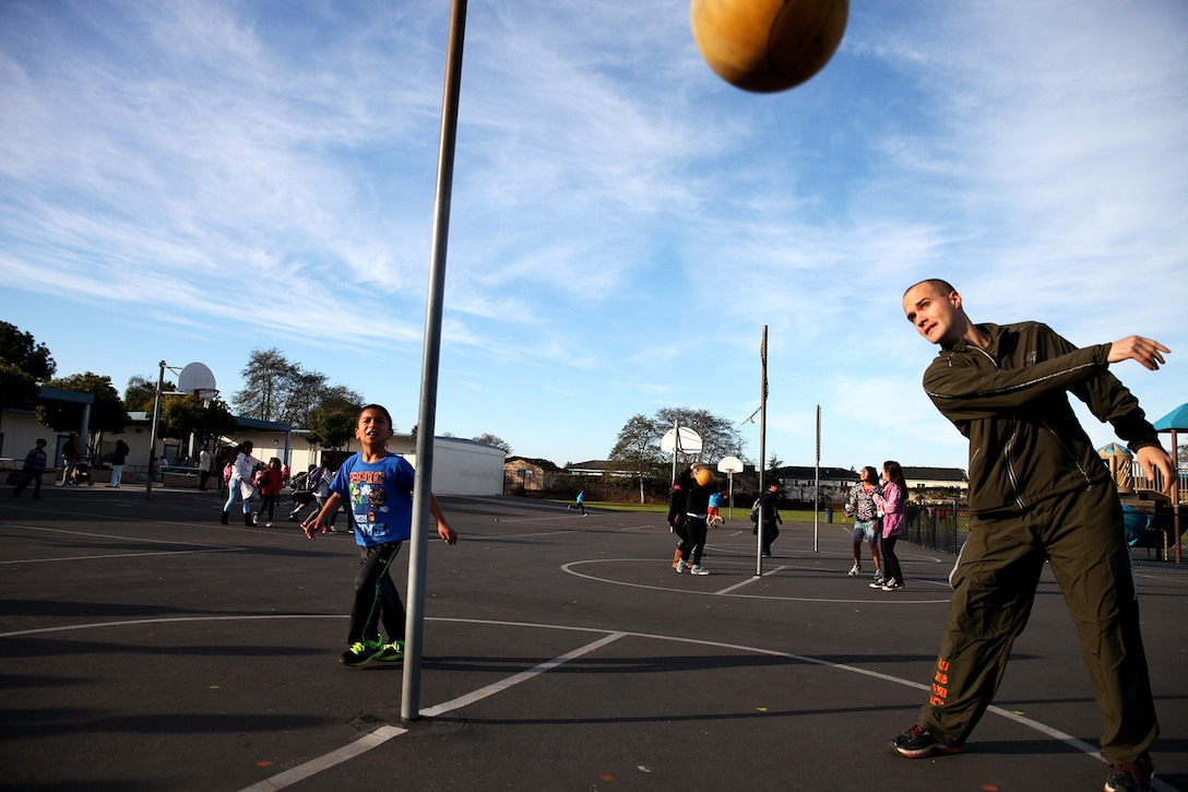 "Sergeant David Perry, a motor transportation mechanic with 1st Medical Battalion, 1st Marine Logistics Group, plays tether ball with a student during a morning workout at Jefferson Elementary School, Feb. 13, 2014. Marines with Combat Logistics Regiment 1 and 1st Medical Bn., volunteered their time to support more than 500 students in their new fitness program known as ""Motion."" During their stay Marines led various events, such as push-ups, squats, soccer and basketball."