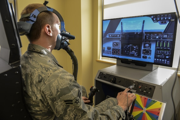 Airman 1st Class Erich Held demonstrates how pilots would use the Reduced Oxygen Breathing Device at the McChord Clinic, Feb. 5, 2014, Joint Base Lewis-McChord, Wash. The ROBD is combined with a flight simulator that can change its heads up display to match the specific aircraft the training pilot flies. Held is a 62nd Medical Squadron optometry technician. (U.S. Air Force photo/Tech. Sgt. Sean Tobin)