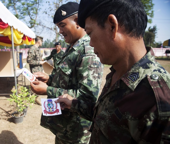 Royal Thai Army soldiers receive Cobra Gold stickers before a dedication ceremony Feb. 19 at the Ban Sa la Kai Fub School as part of Exercise Cobra Gold 2014 in Sukhothai, Kingdom of Thailand. During the exercise, four schools were constructed throughout Thailand. CG 14, in its 33rd iteration, demonstrates the U.S. and the Kingdom of Thailand's commitment to their long-standing alliance and regional partnership, prosperity and security in the Asia-Pacific region.