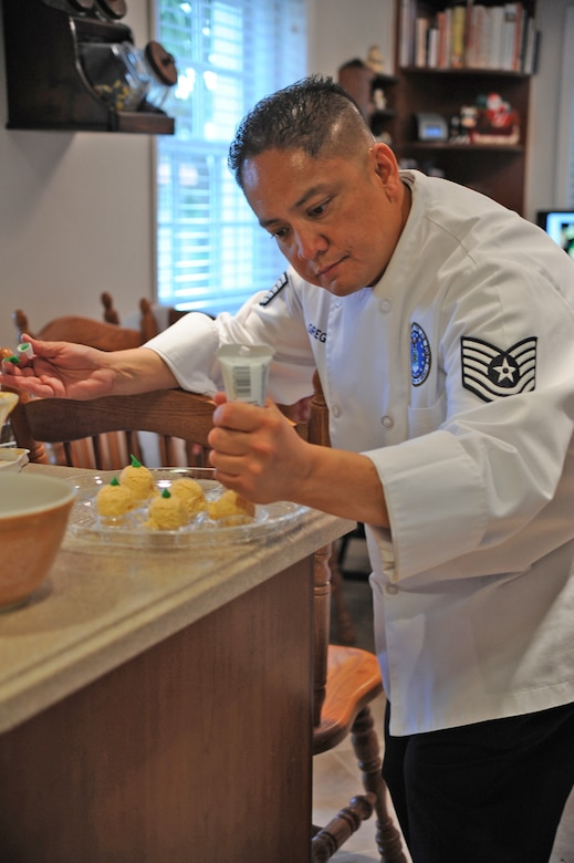 Master Sergeant Jessie Gregorio puts the finishing touches on food to be served at a party. (Photo by Sarah Corrice)