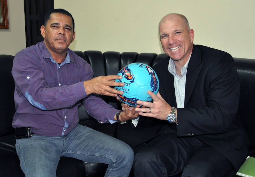 """U.S. Army Col. Thomas Boccardi, Commander, Joint Task Force-Bravo, presents a """"Kick for Nick"""" soccer ball to Jose Tejeda, Mayor of the city of Cane, Honduras, Feb. 19, 2014.  Boccardi spent the day meeting with leaders of several communities surrounding Soto Cano Air Base.  During the meetings, Boccardi presented each leader with more than twenty soccer balls and a collection of soccer jerseys donated from the """"Kick for Nick"""" non-profit organization, which collects and distributes soccer balls for underprivileged children in honor of fallen U.S. Army Pvt. Nick Madaras, who was killed in Iraq in 2006."""