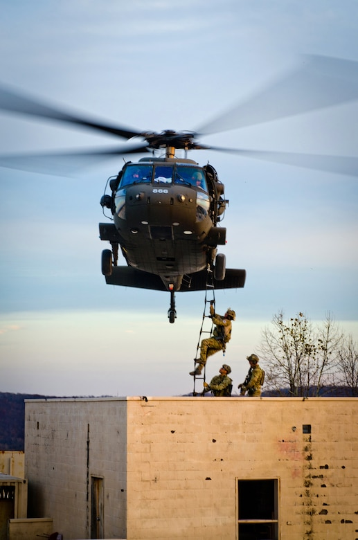 Members of the Kentucky Air National Guard's 123rd Special Tactics Squadron climb a rope ladder onto a Kentucky Army National Guard UH-60 Blackhawk during training at Zussman Range at Fort Knox, Ky., on Nov. 21, 2013. The Airmen were practicing insertions, extractions and close-quarters combat in a simulated Afghan village. (U.S. Air National Guard photo by Master Sgt. Phil Speck)