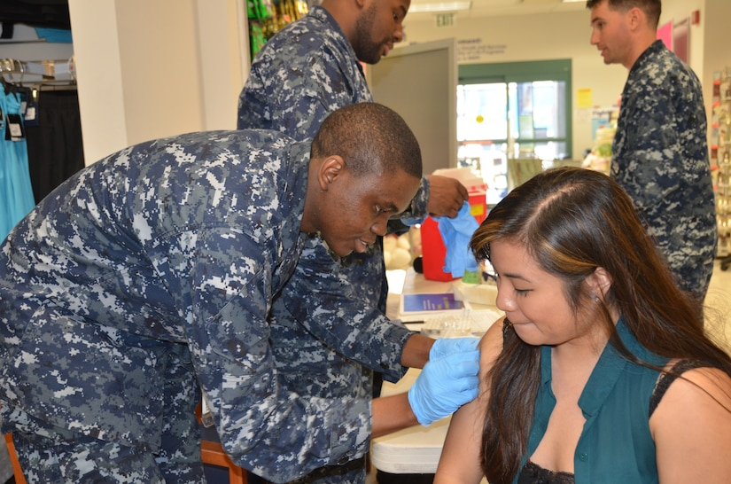 Petty Officer 2nd Class David Oba, Naval Health Clinic Charleston preventative medicine technician, administers a flu vaccination to a patient during a flu vaccination clinic Feb. 6, 2014, at the Navy Exchange on Joint Base Charleston - Weapons Station. (U.S. Navy photo/Eric Sesit)
