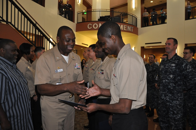 Navy Capt. Marvin Jones, Naval Health Clinic Charleston commanding officer, congratulates Petty Officer 2nd Class David Oba, NHCC preventive medicine technician during a frocking ceremony Dec. 10, 2014, at NHCC on Joint Base Charelston - Weapons Station.